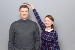 Studio shot of short woman standing on tiptoes and showing height of tall man, both are cheerful and smiling, over gray background. Concept of diversity of people's heights, tall and short persons