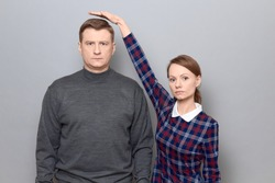 Studio shot of short woman standing on tiptoes and showing height of tall man, both are with serious expressions, over gray background. Concept of diversity of people's heights, tall and short persons