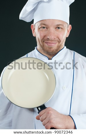 Studio shot of smiling chef with a frying pan