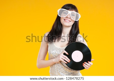 Studio shot of smiling girl in funny eyeglasses with a vinyl disc