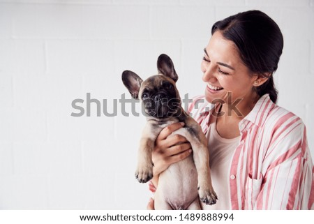 Studio Shot Of Smiling Young Woman Holding Affectionate Pet French Bulldog Puppy