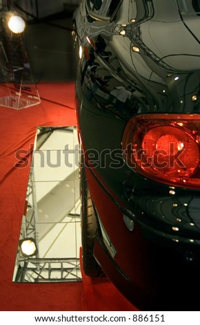 studio shot of sports car with people admiring it