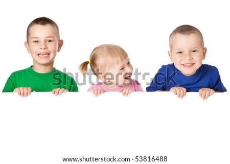 studio shot of three child behind white board