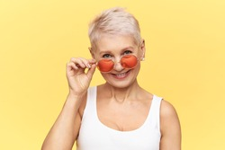 Studio shot of trendy glamorous middle aged female with pixie haircut posing isolated taking off her stylish round sunglasses. Attractive mature woman wearing shades to protect eyes against UV rays