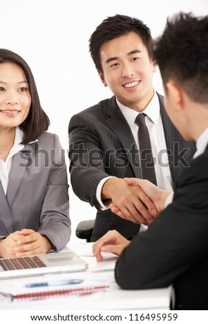 Studio Shot Of Two Chinese Businessmen Shaking Hands During Meeting