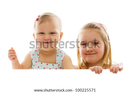 studio shot of two sisters behind white board
