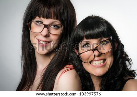 Studio shot of two smiling girls with glasses on gray background