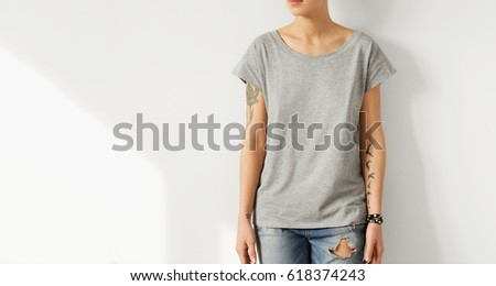 Studio shot of unrecogizable young European female hipster with perfect slim body dressed in oversize grey t-shirt posing indoors at blank wall with copy space for your text or advertising content Stock fotó ©