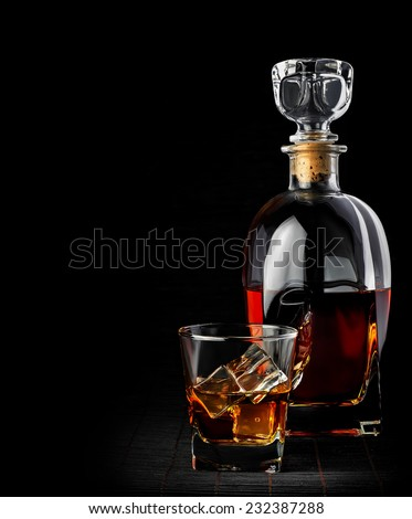 Studio shot of whiskey in a carafe and glass isolated on black