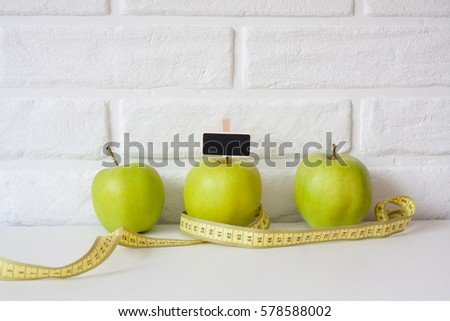 Studio shot of whole green healthy fresh apple with tape measure against white brick wall background. Healthy lifestyle. Diet or weight losing concept. Sport style of life. Scandinavian organic food. #578588002