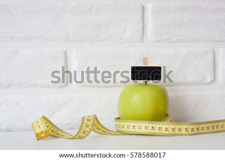 Studio shot of whole green healthy fresh apple with tape measure against white brick wall background. Healthy lifestyle. Diet or weight losing concept. Sport style of life. Scandinavian organic food. #578588017