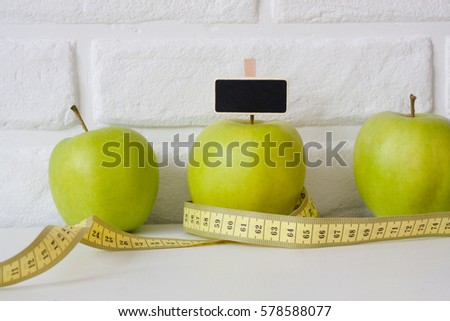 Studio shot of whole green healthy fresh apple with tape measure against white brick wall background. Healthy lifestyle. Diet or weight losing concept. Sport style of life. Scandinavian organic food. #578588077