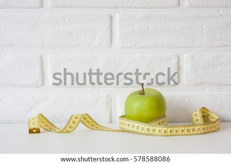 Studio shot of whole green healthy fresh apple with tape measure against white brick wall background. Healthy lifestyle. Diet or weight losing concept. Sport style of life. Scandinavian organic food. #578588086