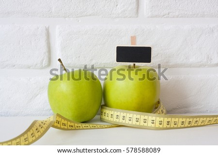 Studio shot of whole green healthy fresh apple with tape measure against white brick wall background. Healthy lifestyle. Diet or weight losing concept. Sport style of life. Scandinavian organic food. #578588089