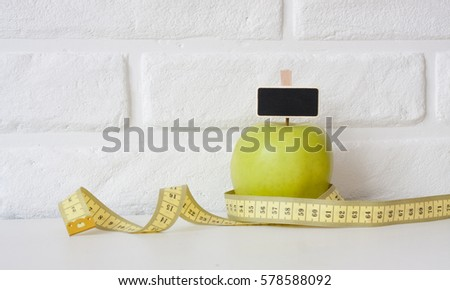 Studio shot of whole green healthy fresh apple with tape measure against white brick wall background. Healthy lifestyle. Diet or weight losing concept. Sport style of life. Scandinavian organic food. #578588092
