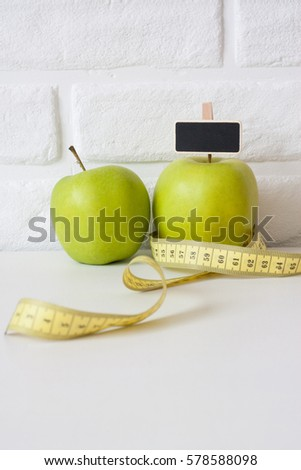 Studio shot of whole green healthy fresh apple with tape measure against white brick wall background. Healthy lifestyle. Diet or weight losing concept. Sport style of life. Scandinavian organic food. #578588098