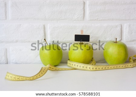 Studio shot of whole green healthy fresh apple with tape measure against white brick wall background. Healthy lifestyle. Diet or weight losing concept. Sport style of life. Scandinavian organic food. #578588101