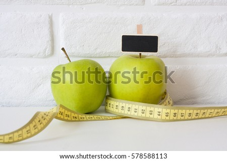 Studio shot of whole green healthy fresh apple with tape measure against white brick wall background. Healthy lifestyle. Diet or weight losing concept. Sport style of life. Scandinavian organic food. #578588113