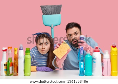 Studio shot of woman and man look scrupulously at camera, do housework, clean everything, hold sponge and broom, sit at workplace with detergents, isolated over pink background. Household duties #1361558486