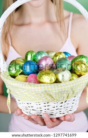 Studio shot of woman holding basket full of chocolate Easter eggs