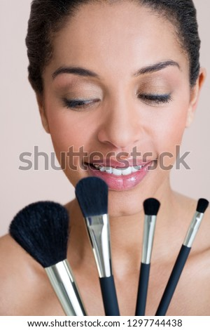 Studio shot of woman holding four different sized make up brushes