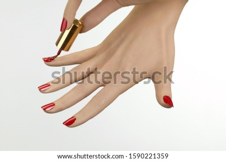 Studio shot of woman painting fingernails