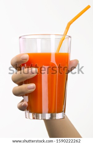 Studio shot of woman's hand holding glass of juice with straw