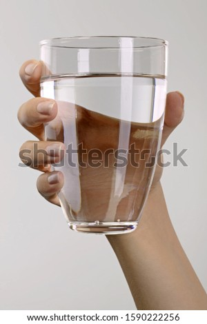 Studio shot of woman's hand holding glass of water