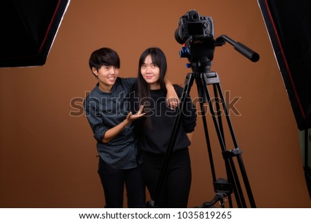 Studio shot of young Asian lesbian couple together and in love against brown background - Shutterstock ID 1035819265