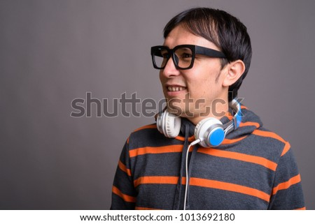 Studio shot of young Asian nerd man wearing hoodie and headphones against gray background
