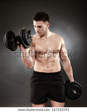 Studio shot of young athletic man working out his biceps with heavy dumbbells