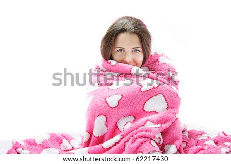studio shot of young attractive woman wrapped in pink blanket