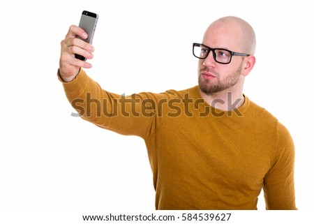 Studio shot of young bald muscular man taking selfie picture with mobile phone