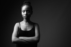 Studio shot of young beautiful African Zulu woman against black background in black and white