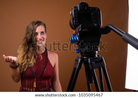 Studio shot of young beautiful Hispanic woman against brown background - Shutterstock ID 1035095467
