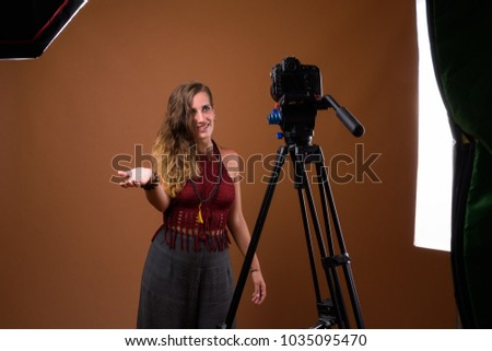 Studio shot of young beautiful Hispanic woman against brown background - Shutterstock ID 1035095470