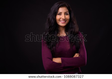 Studio shot of young beautiful Indian woman against black background