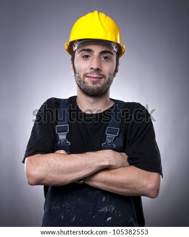Studio shot of young construction worker with arms crossed