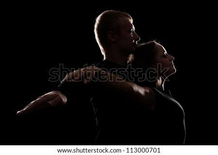 studio shot of young couple in love over dark background