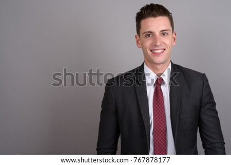 Studio shot of young handsome businessman wearing suit against gray background #767878177