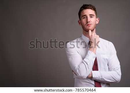 Studio shot of young handsome businessman wearing white shirt and red tie against gray background