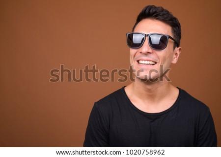 Studio shot of young handsome Hispanic man wearing black shirt against brown background