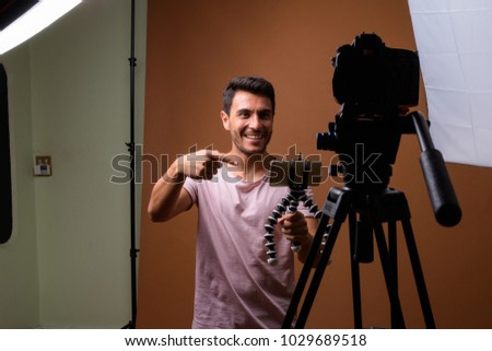 Studio shot of young handsome Hispanic man wearing pink shirt against brown background - Shutterstock ID 1029689518