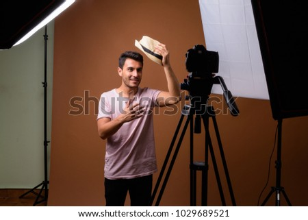 Studio shot of young handsome Hispanic man wearing pink shirt against brown background - Shutterstock ID 1029689521