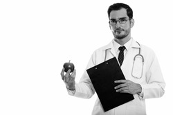 Studio shot of young handsome man doctor holding clipboard and apple