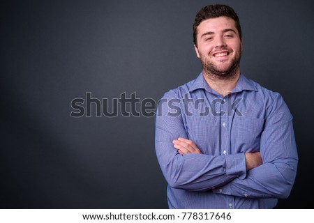 Studio shot of young handsome overweight businessman against gray background