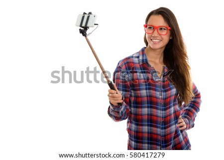 Studio shot of young happy woman smiling while holding selfie stick and taking selfie picture with mobile phone