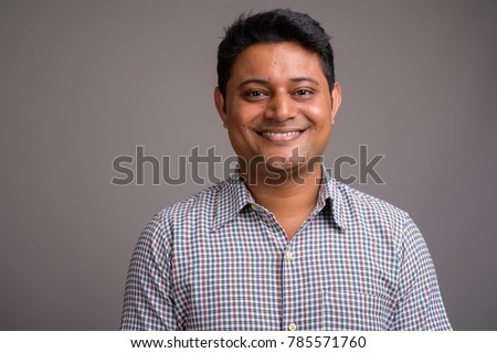 Studio shot of young Indian businessman wearing checkered shirt against gray background #785571760