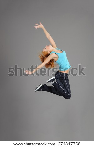 Studio shot of young  jumping woman in casual clothing