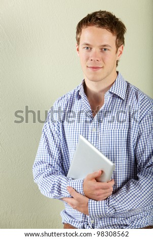 Studio Shot Of Young Man Holding Tablet Computer
